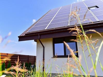 Blick auf ein Einfamilienhaus aus dem Garten, auf dem Dach befindet sich eine Photovoltaik-Anlage.