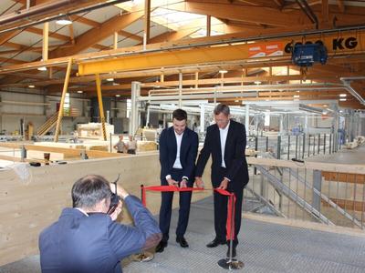 Geschäftsführer Haas Fertigbau, beim durchschneiden des Eröffnungsbandes